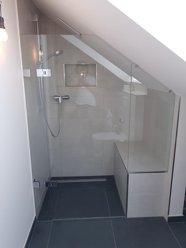 Badaufteilung mit einer Dusche in einer Nische festes Teil und Türe daran Flamea unter Dachschräge
